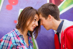 Les jeunes couples s'approchent du fond de graffiti. Photo stock