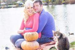 Les jeunes couples s'approchent du lac avec le potiron, temps d'automne image libre de droits