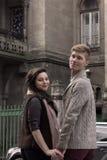 Les jeunes couples se prennent par les mains sur la rue Image stock