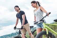 Les jeunes couples se reposant après vélo montent dans le domaine Fin vers le haut images stock