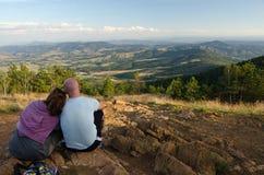 Les jeunes couples se reposant sur la montagne complètent en été Photographie stock