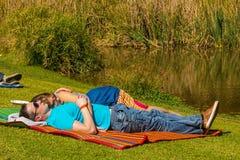 Les jeunes couples se trouvant sur une couverture de pique-nique à l'hiver sculptent F Photographie stock