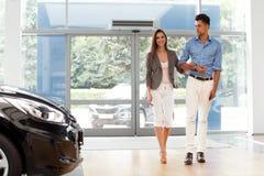 Les jeunes couples sont entrés dans la salle d'exposition de voiture Salon automatique Image libre de droits