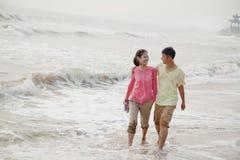 Les jeunes couples souriant et marchant par les eaux affilent sur la plage, Chine Photographie stock