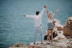Les jeunes couples sur la plage d'océan appréciant leurs vacances d'été, bras se sont étendus vers le soleil comme symbole de la  image libre de droits