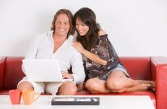 Les jeunes couples sur le sofa jouent avec l'ordinateur portatif Photographie stock libre de droits