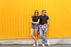 Les jeunes couples utilisant les T-shirts noirs s'approchent du mur de couleur image stock