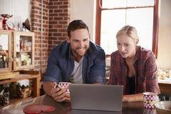 Les jeunes couples utilisant un ordinateur portable dans la cuisine, se ferment, vue de face Photo stock