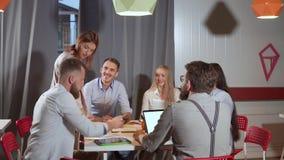 Les jeunes créatifs discutent dans des bureaux, le sourire et rire clips vidéos