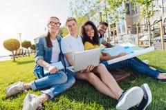 Les jeunes décontractés s'asseyant sur l'herbe Photographie stock libre de droits