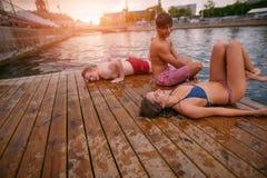 Les jeunes détendant sur la jetée Image stock