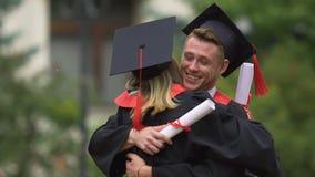 Les jeunes dans des robes scolaires embrassant gaiement, échangeant des félicitations banque de vidéos