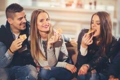 Les jeunes dans des vêtements sport mangeant de la pizza Image libre de droits