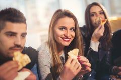 Les jeunes dans des vêtements sport mangeant de la pizza Photos libres de droits