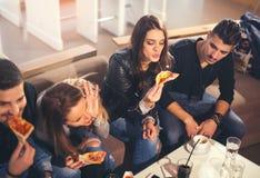 Les jeunes dans des vêtements sport mangeant de la pizza Image stock