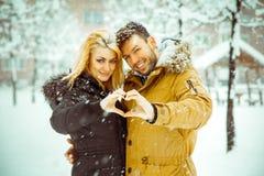 Les jeunes dans l'amour caressant et signes d'exposition d'un f en forme de coeur Image libre de droits