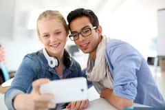 Les jeunes dans l'université prenant le selfie Image libre de droits