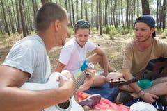 Les jeunes dans la forêt jouant la guitare Images libres de droits