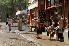 Les jeunes dans le café extérieur au centre historique d'Amsterdam Photographie stock libre de droits