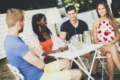 Les jeunes dans le café à l'été Image stock