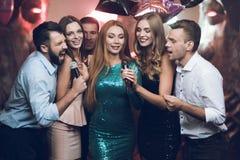 Les jeunes dans le club dansent et chantent Un homme dans une chemise blanche tient un microphone et un chant Photos stock