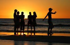Les jeunes dans le coucher du soleil Image stock