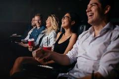 Les jeunes dans le film et le sourire de observation de théâtre Images libres de droits