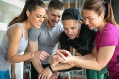 Les jeunes dans le gymnase Séance d'entraînement d'amis dans le gymnase et à l'aide du téléphone intelligent Photographie stock libre de droits