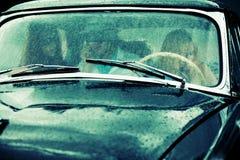 Les jeunes dans le rétro véhicule sous la pluie Images stock