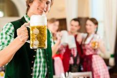 Les jeunes dans Tracht bavarois traditionnel dans le restaurant ou le bar Photographie stock