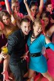 Les jeunes dansant dans le club ou la disco, les hommes et les femmes Images stock
