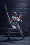 Les jeunes danseurs exécutant dans l'obscurité ont allumé la pièce Photographie stock