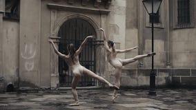 Les jeunes danseurs féminins professionnels exécute la danse acrobatique le long de la rue médiévale sous la pluie Filles humides banque de vidéos