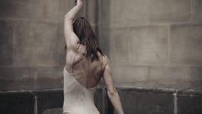 Les jeunes danseurs féminins professionnels exécute la danse acrobatique le long de la rue médiévale sous la pluie Filles humides clips vidéos