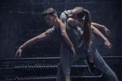 Les jeunes danseurs fatigués dans l'obscurité ont allumé la pièce Photo libre de droits