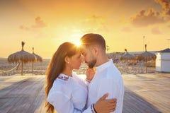 Les jeunes de couples dans l'amour étreignent sur la plage Photographie stock
