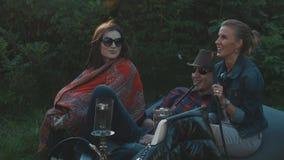 Les jeunes de détente fument le narguilé, parlant, riant se reposer dehors banque de vidéos