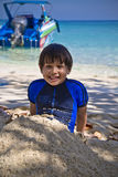 Les jeunes de sourire heureux ont mélangé le garçon asiatique emballé sur la plage se reposant sur le sable Image libre de droits