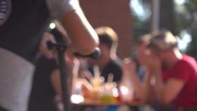 Les jeunes Defocused mangeant des aliments de préparation rapide extérieurs vidéo de bokeh du fond 4K banque de vidéos