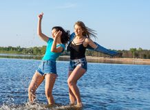 Les jeunes, deux femmes, étudiantes sont heureux sur la plage Photo libre de droits