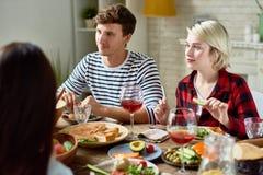 Les jeunes dinant avec des amis à la maison Photo stock