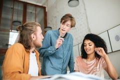 Les jeunes discutant quelque chose dans le bureau Deux garçons avec les cheveux blonds et la fille avec l'étude bouclée foncée en Image stock