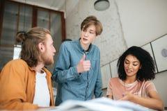 Les jeunes discutant quelque chose dans le bureau Deux garçons avec les cheveux blonds et la fille avec l'étude bouclée foncée en Photos libres de droits