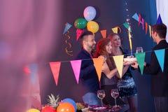 Les jeunes donnant le gâteau d'anniversaire Image libre de droits