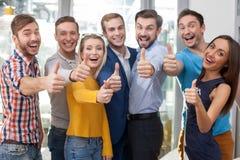 Les jeunes employés de bureau gais font des gestes Photographie stock libre de droits