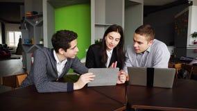 Les jeunes employés de la société sont des femmes et des hommes faisant des tables et c images libres de droits