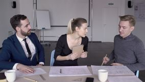 Les jeunes employés travaillent à la table dans le bureau moderne à l'intérieur banque de vidéos