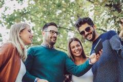 Les jeunes en parc avec le comprimé numérique ayant l'amusement Images libres de droits