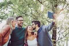 Les jeunes en parc avec le comprimé numérique ayant l'amusement Photos libres de droits
