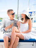 Les jeunes et beaux couples ont une partie sur un bateau à voile de luxe Photos stock